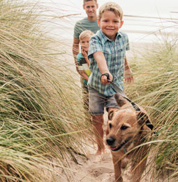 children walking dog on the beach